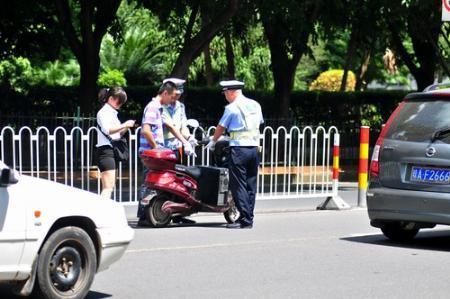未悬挂号牌电动车在机动车道上行驶被处罚.高清图片